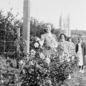 Four women in garden with St Johns College in background
